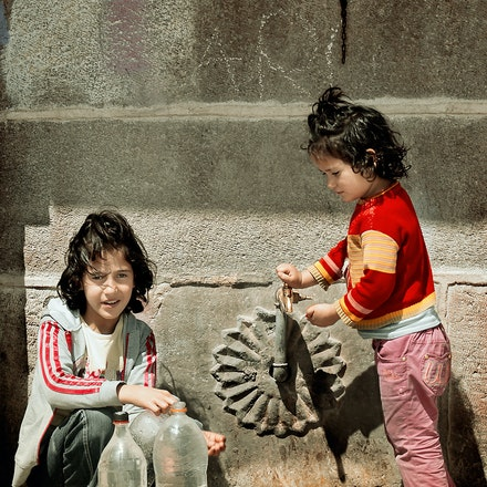 Family Water Collection - Two young girls collect water from the village tap for the family. Eastern Turkey.